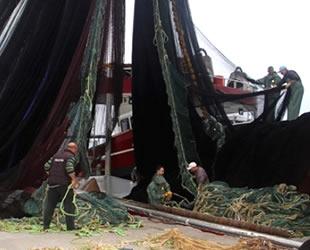 Karadenizli balıkçılar ağlarını hamsi avı için onarıyor